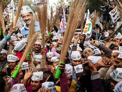 aap-supporters-hold-brooms-delhi-elections (1)